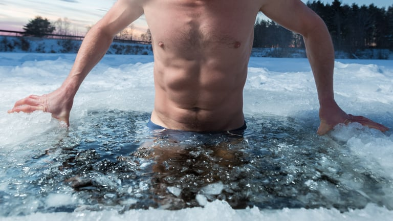 Man getting into an ice bath in nature